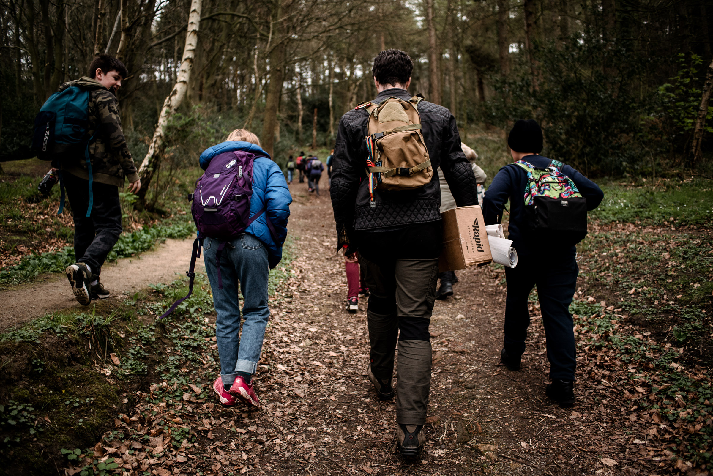 Image of children with an adult walking through the woods